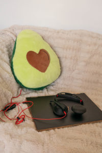 Picture of a laptop with headphones and an avocado cushion on a couch