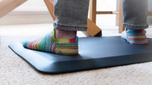 two feet in brightly coloured socks standing on a support mat