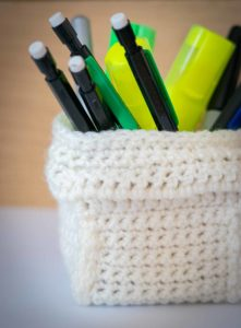 A crocheted pencil pot containing an  assortment of pens and pencils