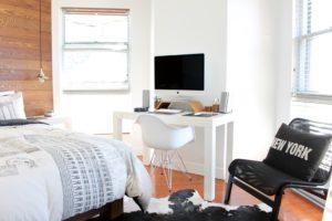 a white desk set up in a bedroom
