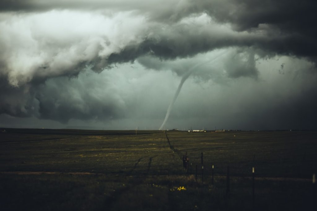 Picture of a tornado in a dark sky above a field