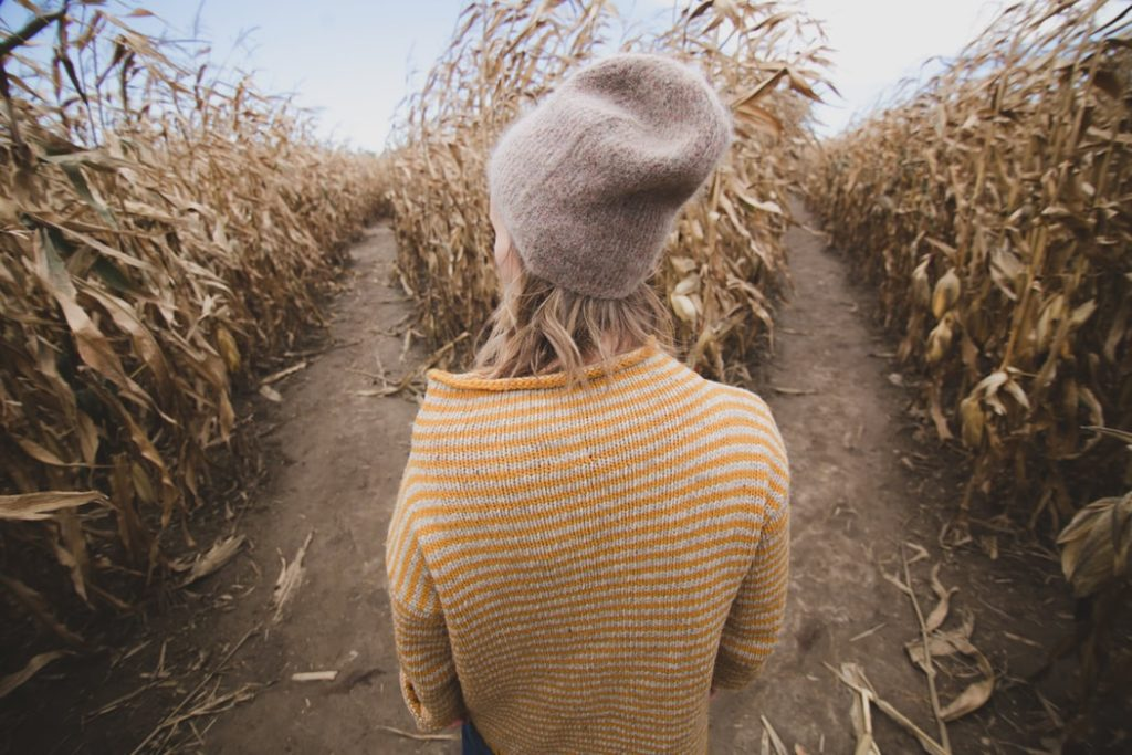 lady standing between two rows of corn