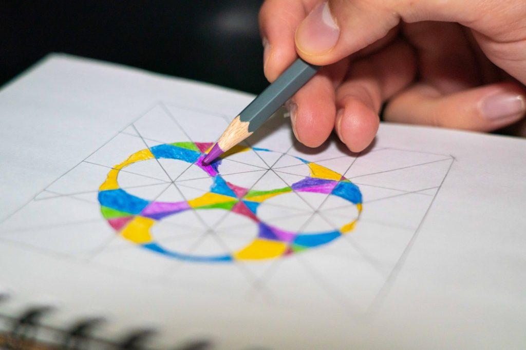 hand holding a coloring pencil coloring a mandala