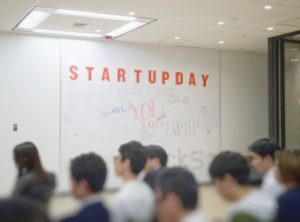 A group of people in a room with the words 'Start up day' on the wall
